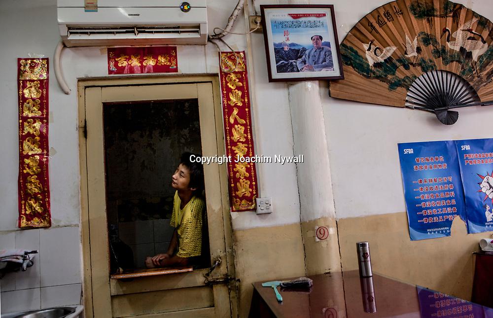 2011 08 Beijing Kina China Peking<br /> Kille som tittar ut genom en d&ouml;rr p&aring; en liten restaurang<br /> <br /> <br /> ----<br /> FOTO : JOACHIM NYWALL KOD 0708840825_1<br /> COPYRIGHT JOACHIM NYWALL<br /> <br /> ***BETALBILD***<br /> Redovisas till <br /> NYWALL MEDIA AB<br /> Strandgatan 30<br /> 461 31 Trollh&auml;ttan<br /> Prislista enl BLF , om inget annat avtalas.