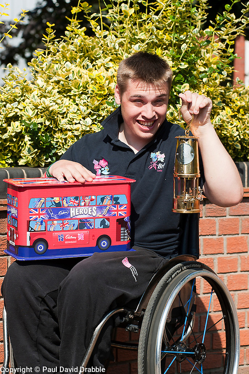 Cadbury 2012 Paralympic demonstration Sheffield..Torch Bearer and member of the RGK Rhinos Sporting club wheelchair basketball team Josh Dunn with the paralympic torch and Cadbury Heroes Olympic Bus outside Kraft Foods (formerly Basset's factory) Sheffield...3 September 2012.Image © Paul David Drabble