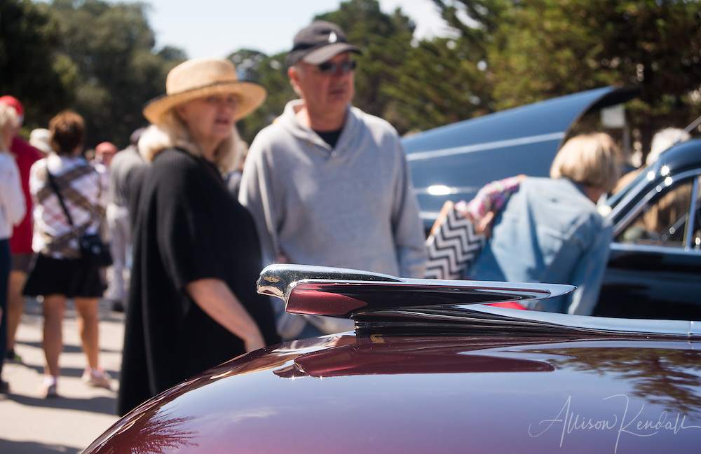 Detail of hood ornament with spectators at the Carmel-by-the-Sea Concours on the Avenue during Monterey Car Week