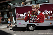 A Tesco delivery van for online purchases and woman passer-by in the City of London - the capital's financial district, on 6th June 2018, in London, England.