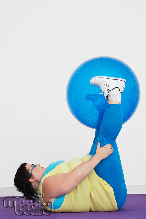 Overweight Woman lying down lifting exercise ball with legs