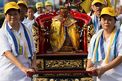 © Licensed to London News Pictures. 28/09/2014. Ipoh, Malaysia. Devotees carry a deity as they process through the streets of central Ipoh, Malaysia on the 5th day of the Nine Emperor Gods Festival, Sunday, Sept. 28, 2014. The festival is a nine-day Taoist celebration to mark the birth of the Nine Emperor Gods from the first day to the ninth day of the ninth moon in Chinese Lunar Calender. The origin of the Nine Emperor Gods (stars of the Northern constellation) can be traced back to the Taoist worship of the Northern constellation during Qin and Han Dynasty and absorb this practice of worshipping the stars and began to deitify them as Gods. Photo credit : Sang Tan/LNP