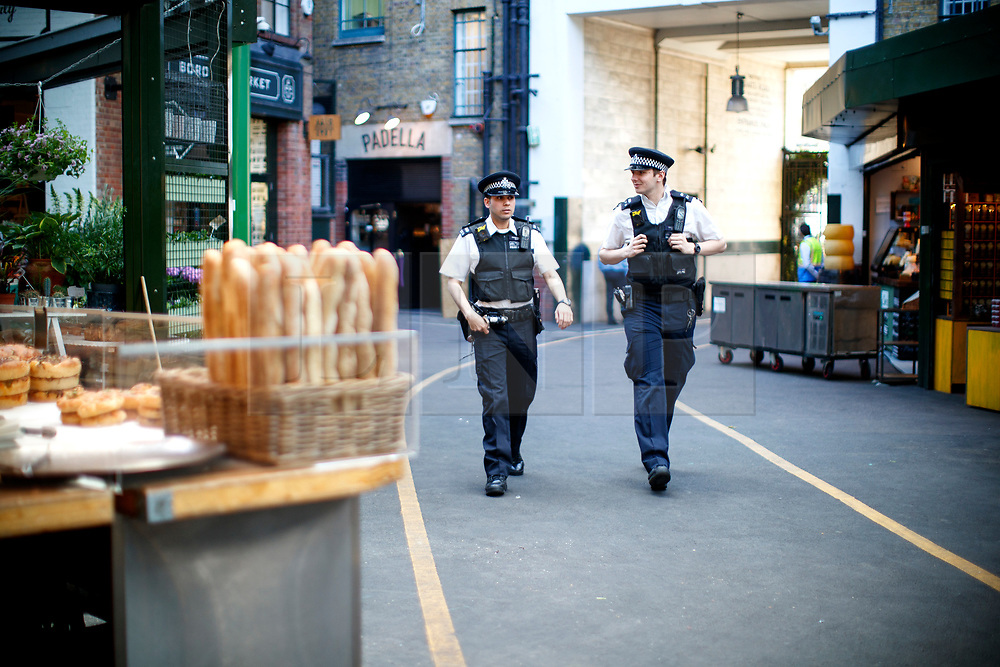 © Licensed to London News Pictures. 14/06/2017. London, UK. Police officers patrol as shop owners and traders getting ready for the reopening of Borough Market in London on 14 June 2017, following a terror attack that killed 8 people over a week ago. Photo credit: Tolga Akmen/LNP