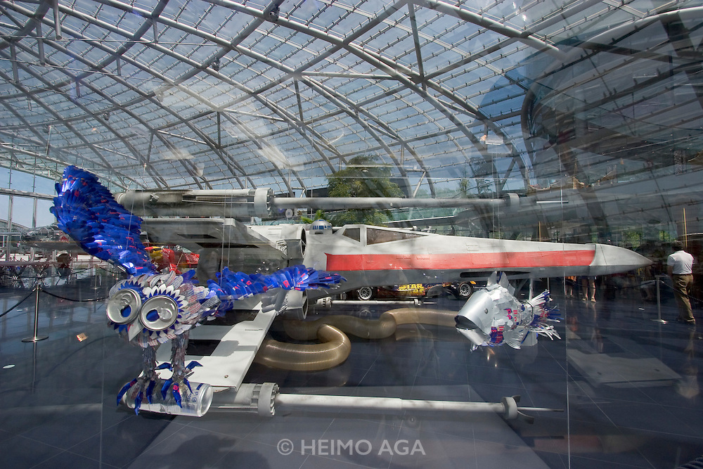 """Hangar-7; the spectacular home of the Flying Bulls (""""Red Bull"""" owner Didi Mateschitz' collection of classic airplanes) next to Salzburg W.A. Mozart airport. Original X-Wing Starfighter from """"Star Wars"""" parked next to a Red Bull Formula One racing car themed """"Star Wars Episode III: Revenge of the Sith"""", as driven by David Coulthard and Vitantonio Liuzzi in the 2005 Monaco Grand Prix. Red Bull Can Art Worldwide special exhibition. """"Please don't feed the birds""""."""