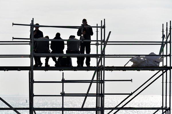 Nederland, Kornwerderzand, 22-2-2018Jonge bouwvakkers pauzeren, schaften, hebben pauze, schaft, op de bouw van het waddencenter, het beleefcentrum de nieuwe afsluitdijk, wadden center .Dit centrum biedt een totaalbeleving over Unesco Werelderfgoed Waddenzee, de Vismigratierivier, het IJsselmeergebied en de Afsluitdijk zelf .Foto: Flip Franssen