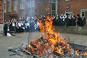 Orthodox Jewish schoolboys from the Bobov school celebrate Lag B'Omer with a bonfire in the school playground. Lag B'Omer is the holiday celebrating the thirty-third day of the (counting of the) Omer. Jews celebrate it as the day when the plague that killed 24,000 people ended in the holy land (according to the Babylonian Talmud). Other sources say the plague was actually the Roman occupation and the 24,000 people died in the second Jewish - Roman war  (Bar Kokhba revolt of the first century).  Bonfires (used as signals in wartime) are symbolically lit to commemorate the holiday of Lag'B'Omer.