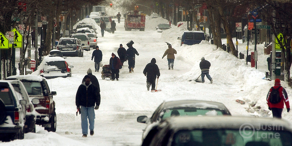 Pedestrians are seen outnumbering cars on a street in Brooklyn, NY following a major winter storm Sunday, 23 January 2005. The storm dumped over a foot of snow, over two in some places, on the Eastern United States, causing nearly 500 flights to be canceled Sunday morning at the New York metropolitan area's Newark, Kennedy and LaGuardia airports.