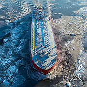 January 30, 2014 - New York, NY : A large ship is pushed by a tug boat up the frozen Hudson River -- breaking ice floes as it goes -- near the George Washington Bridge between New York City and New Jersey, at sunset in January.  CREDIT: Karsten Moran / Aurora Photos