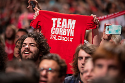 © Licensed to London News Pictures. 26/09/2018. Liverpool, UK. A Labour Party supporter holds up a 'TEAM CORBYN' t-shirt as Labour Leader Jeremy Corbyn MP comes on to the stage to deliver his speech at the end of the Labour Party Conference. Photo credit: Rob Pinney/LNP