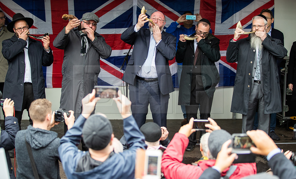 © Licensed to London News Pictures . 16/09/2018. Manchester, UK. Five rabbis on the stage blow the Shofar in a symbolic call to eradicate anti-Semitism . Thousands of people including the UK's Chief Rabbi and several Members of Parliament attend a demonstration against rising anti-Semitism in British politics and society , at Cathedral Gardens in Manchester City Centre . Photo credit : Joel Goodman/LNP