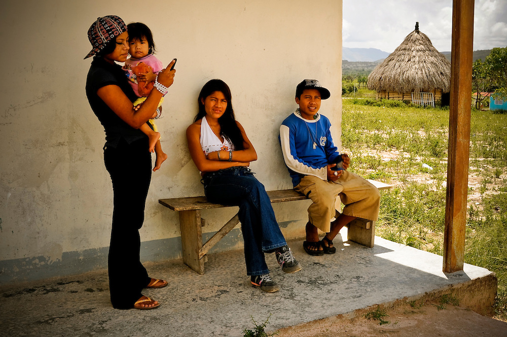 (Left to right) Siblings Tomasa Fernandez, 18, Angelica Fernandez, 1, Maria Fernandez, 19, and Jose Fernandez, 15, listen to reggaeton and talk on cell phones in front of their home in the San José de Wará  indigenous Pemón village in Canaima National Park in Venezuela's Gran Sabana. Many young Pemón have assimilated and embrace modern pop culture.