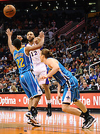Apr 7, 2013; Phoenix, AZ, USA; Phoenix Suns guard Kendall Marshall (12) makes a pass against the New Orleans Hornets guard Brian Roberts (22) and forward Lou Amundson (17) in the first half at US Airways Center. Mandatory Credit: Jennifer Stewart-USA TODAY Sports