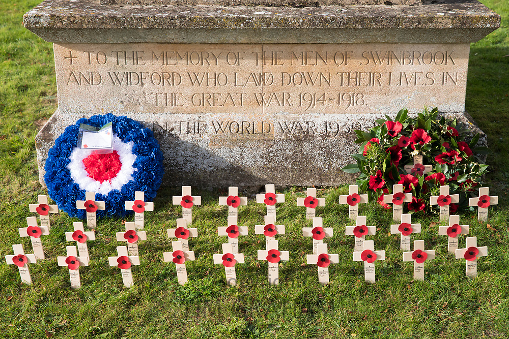 Remembrance wreath and crosses with poppies at war memorial for The Great War 1914-1918 - World War I and World War II 1939-1945 in the graveyard of St Mary's Church, Swinbrook commemorating those who died from the parish of Swinbrook and Widford, Oxfordshire, UK