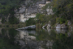 Stock photo of boulder sticking out from the water in a river in the Texas Hill Country