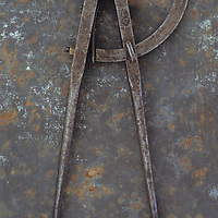 Pair of vintage tarnished measuring dividers or compasses lying on rusty metal sheet
