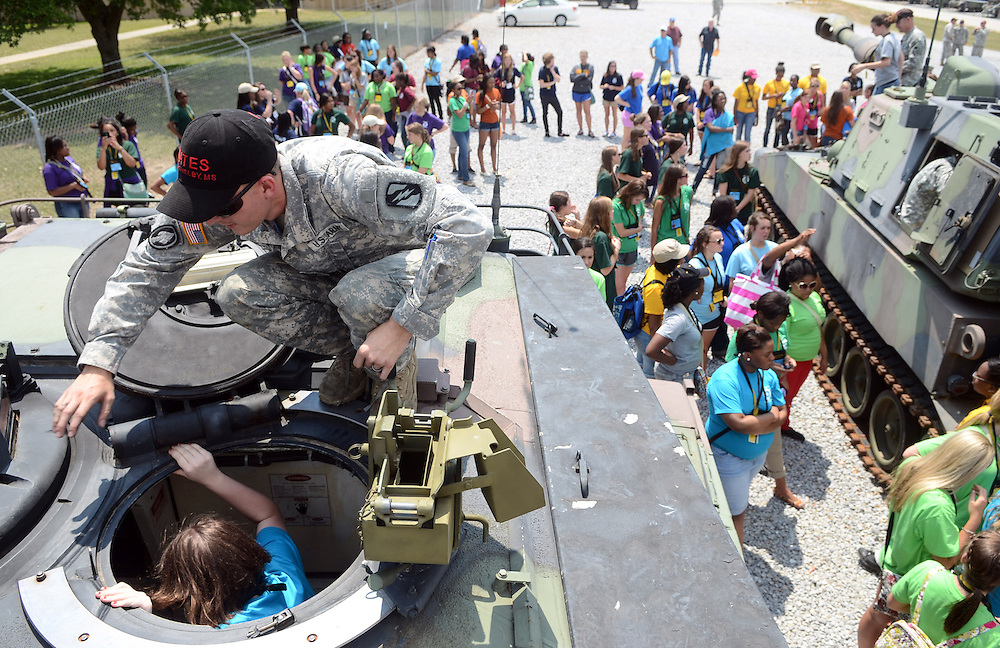 Spec. Joseph Ethredge helps members Girl's State into tanks on Thursday during a tour of Camp Shelby's Mobilization and Training Equipment Site. The program brought over 200 girls to visit Camp Shelby for the afternoon. Bryant Hawkins/The Hattiesburg American