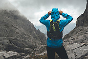 Back view of a trail runner wearing a hooded jacket on a rainy day close to Collado Jermoso, Leon, Spain Trail runner running uphill in Collado Jermoso, Picos de Europa National Park, Spain