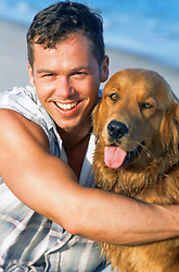 man holding a golden retriever at the beach