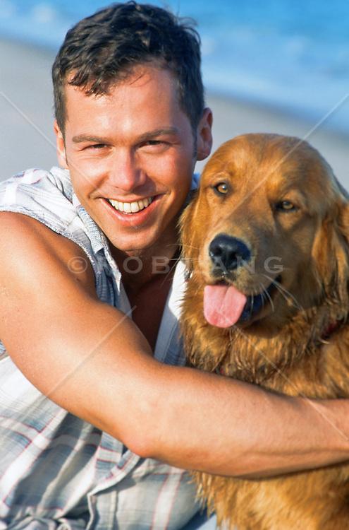 man holding a golden retriever at the beach