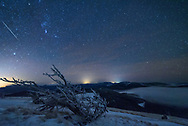 For the Geminid meteor shower I snowshoed to the top of the continental divide in Western Montana. From the Granite Butte lookout tower, the views were stunning in every direction. The weather changed by the second alternating between snow showers, gale force winds, freezing fog with zero visibility, clear skies, and brief moments of calm. The tough whitebark pine trees which grow up here are all permanently bent. They point eastward from the prevailing westerly winds which almost never stop. The low temperatures, strong winds, and fog combined to create hard rime ice, which covered every surface (including me and my camera) with a coating up to 2 inches thick. To say that shooting conditions were challenging would be an understatement. My tripod had to be carefully propped up to avoid it blowing over. And with all my batteries dying too soon, I didn't get to take as many pictures as I wanted to. But this was one of the brighter meteors captured, flying in between Orion and Sirius.