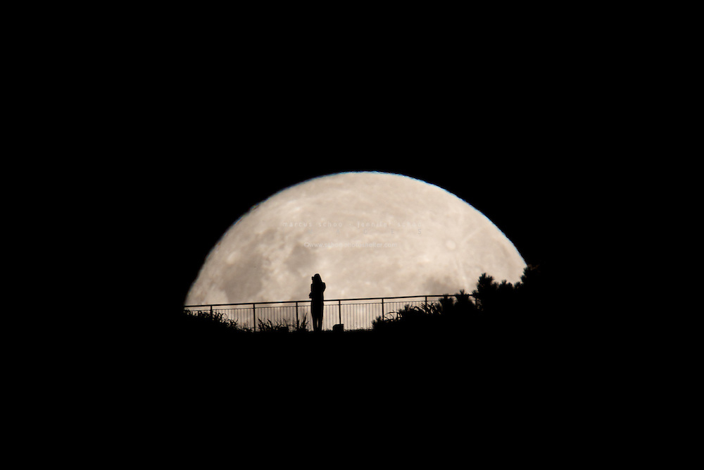 A woman looks upon the full moon in Wellington New Zealand.