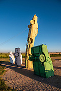 """In the Car Art Reserve at Carhenge, Jim Reinders arranged the """"Ford Seasons"""" artwork using four Fords as inspired by Vivaldi's Four Seasons. Carhenge replicates England's Stonehenge using vintage American automobiles, near Alliance, Nebraska, in the High Plains region, USA. After studying Stonehenge in England, years later, Jim Reinders recreated the physical size and placement of Stonehenge's standing stones in summer 1987, helped by 35 family members. Reinders said, """"It took a lot of blood, sweat, and beers."""" Carhenge was built as a memorial to Reinders' father. 39 automobiles were arranged in the same proportions as Stonehenge with the circle measuring a slightly smaller 96 feet (29m) in diameter. Some autos are held upright in pits five feet deep, trunk end down, while other cars are placed to form the arches and welded in place. All are covered with gray spray paint. The heel stone is a 1962 Cadillac. Reinders donated Carhenge to the Friends of Carhenge, who gifted it to the Citizens of Alliance in 2013."""
