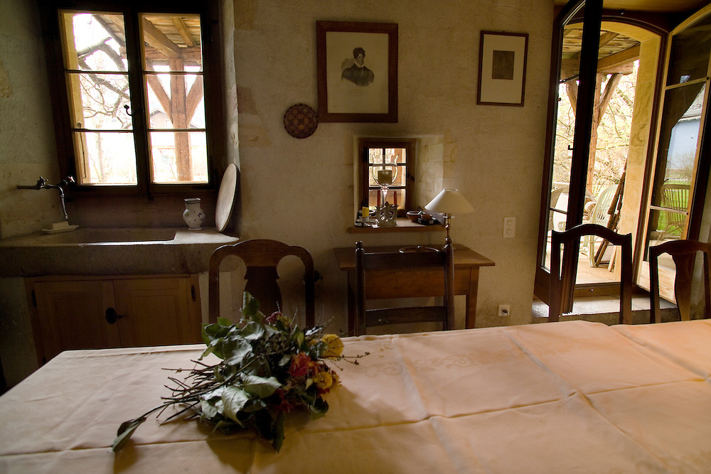 A 1700 Swiss kitchen and dining area in Bovaresse, Switzerland. High backed dining chairs surround a table with a white tablecloth with fold lines and a bunch of roses on top. A sink with a stone countertop and wooden door cabinet is in the corner. Two windows and one double doorway bring light into the room. a small desk is on the back wall below a portrait.