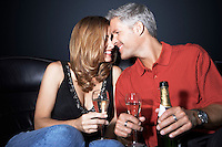 Couple sitting rubbing noses holding champagne glasses