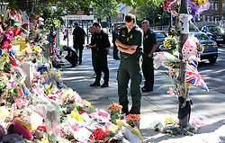 A London Ambulance crew look at the flowers for Lee Rigby at the scene of his murder in Woolwich in South East London, Monday, 27th May 2013 Picture by :  Stephen Lock / i-Images