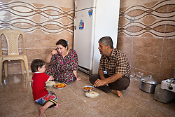 © Licensed to London News Pictures. Hamdaniyah, Iraq. 26/07/2014. Some of the members of a 17 strong Iraqi Christian refugee family eat lunch in the kitchen of the unfinished house they now inhabit in Hamdaniyah, Iraq. The family all left Mosul on Friday the 18th of July when Islamic State fighters issued an ultimatum to the city's Christian community. When the family left they were forced to pay a tax for their car, and one member was threatened at knifepoint to ensure they handed over all of their possessions.<br /> <br /> Having taken over Mosul Iraq's second largest city in June 2014, fighter of the Islamic State (formerly known as ISIS) have systematically expelled the cities Christian population. Despite having been present in the city for more than 1600 years, Christians in the city were given just days to either convert to Islam, pay a tax for being Christian or leave; many of those that left were also robbed at gunpoint as they passed through Islamic State checkpoints.. Photo credit : Matt Cetti-Roberts/LNP