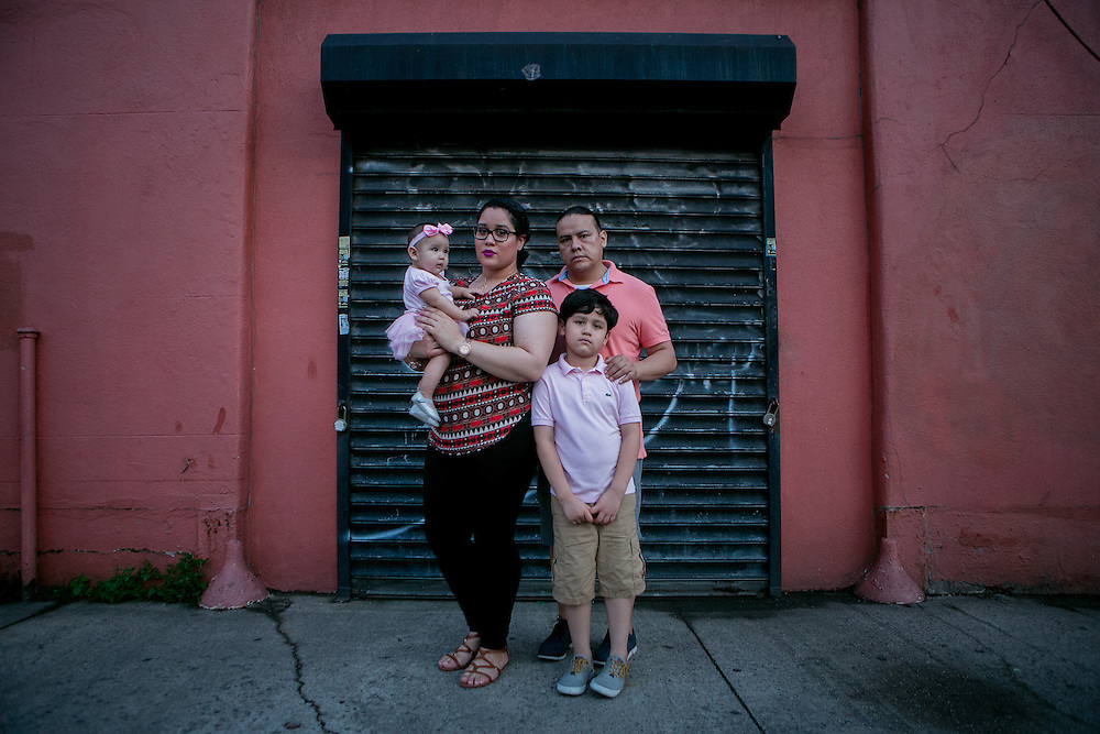 NEW YORK, NY - JULY 7, 2016: Stephanie Arias poses for a portrait with her husband Ricardo Alvarez and children, Ashton Alvarez, 7 and Madison Alvarez, 6 months, on their block, which is still lit with older city lights in Queens, New York. CREDIT: Sam Hodgson for The New York Times.