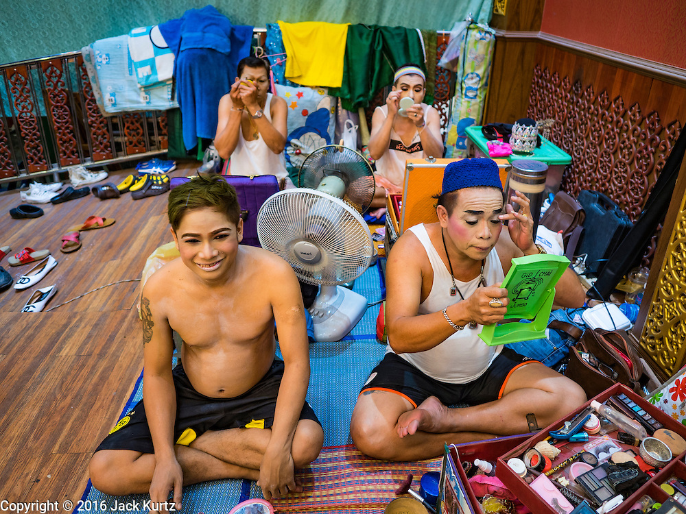 """30 JANUARY 2016 - NONTHABURI, NONTHABURI, THAILAND:  Male performers put on their makeup before a """"likay"""" show at Wat Bua Khwan in Nonthaburi, north of Bangkok. Likay is a form of popular folk theatre that includes exposition, singing and dancing in Thailand. It uses a combination of extravagant costumes and minimally equipped stages. Intentionally vague storylines means performances rely on actors' skills of improvisation. Like better the known Chinese Opera, which it resembles, Likay is performed mostly at temple fairs and privately sponsored events, especially in rural areas. Likay operas are televised and there is a market for bootleg likay videos and live performance of likay is becoming more rare.    PHOTO BY JACK KURTZ"""