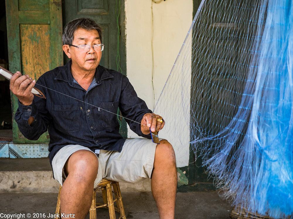 "13 MARCH 2016 - LUANG PRABANG, LAOS: A man repairs his fishing nets in front of his home in Luang Prabang. Scenes like this, once common in the town, are now rare because so many working class Lao people have sold their homes to real estate speculators and moved out of town. Luang Prabang was named a UNESCO World Heritage Site in 1995. The move saved the city's colonial architecture but the explosion of mass tourism has taken a toll on the city's soul. According to one recent study, a small plot of land that sold for $8,000 three years ago now goes for $120,000. Many longtime residents are selling their homes and moving to small developments around the city. The old homes are then converted to guesthouses, restaurants and spas. The city is famous for the morning ""tak bat,"" or monks' morning alms rounds. Every morning hundreds of Buddhist monks come out before dawn and walk in a silent procession through the city accepting alms from residents. Now, most of the people presenting alms to the monks are tourists, since so many Lao people have moved outside of the city center. About 50,000 people are thought to live in the Luang Prabang area, the city received more than 530,000 tourists in 2014.    PHOTO BY JACK KURTZ"