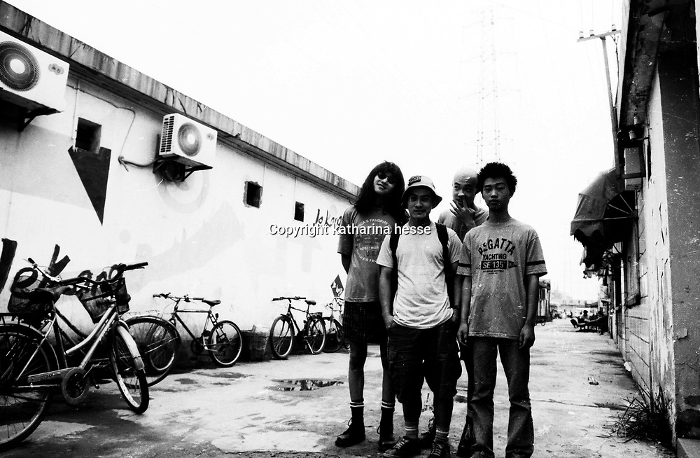 "BEIJING, HAIDIAN DISTRICT,CHINA-AUGUST 15,1999:.a group of punks hang out together in the alley outside the Scream Club before a punk show, August 15, 1999, in China.. In the spring of 1998, a handful of youngsters teamed up to unofficially rebel against conformist Chinese life. They shaved their heads, and founded bands with names like ""Brain Failure"" and ""Anarchy Boys"".  To some like Punker Xiao Rong, this lifestyle was an extension of the life he'd begun as a school dropout at age sixteen.-Although the majority of the punks came from well-off families, they preferred to live in self-imposed poverty. .The Scream Bar and its surrounding dusty alleyways in the student district became the center of youthful rebellion until it was closed . The punks bands have moved on to other bars in Beijing, some got contracts with foreign record companies and even toured Europe, Japan and the"