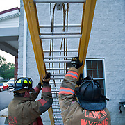 Fire fighters lift a heavy 35 foot fiberglass ladder during ladder training Wednesday, July 6, 2011, in Camden-Wyoming Delaware.