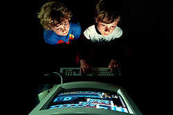 Young boys play a computer game, England, UK.