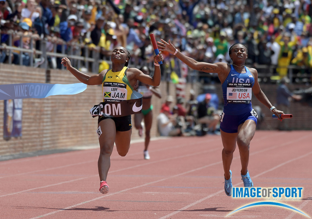 Apr 28, 2018; Philadelphia, PA, USA; Jura Levy of Jamaica (left) celebrates after defeating Kyra Jefferson (USA) on the anchor of the USA vs. The World women's 4 x 100m relay, 43.14 to 43.18, during the 124th Penn Relays at Franklin Field.