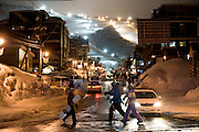 The lights of Grand Hirafu ski resort in the distance, boarders and skiers cross the main street at Hirafu, Japan on Feb. 7 2010. Many of Niseko's 57 ski runs are open until 9 p.m., making Niseko the biggest supplier of night skiing in the world.
