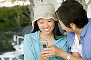 Mother and Smiling Daughter Using Cell Phone