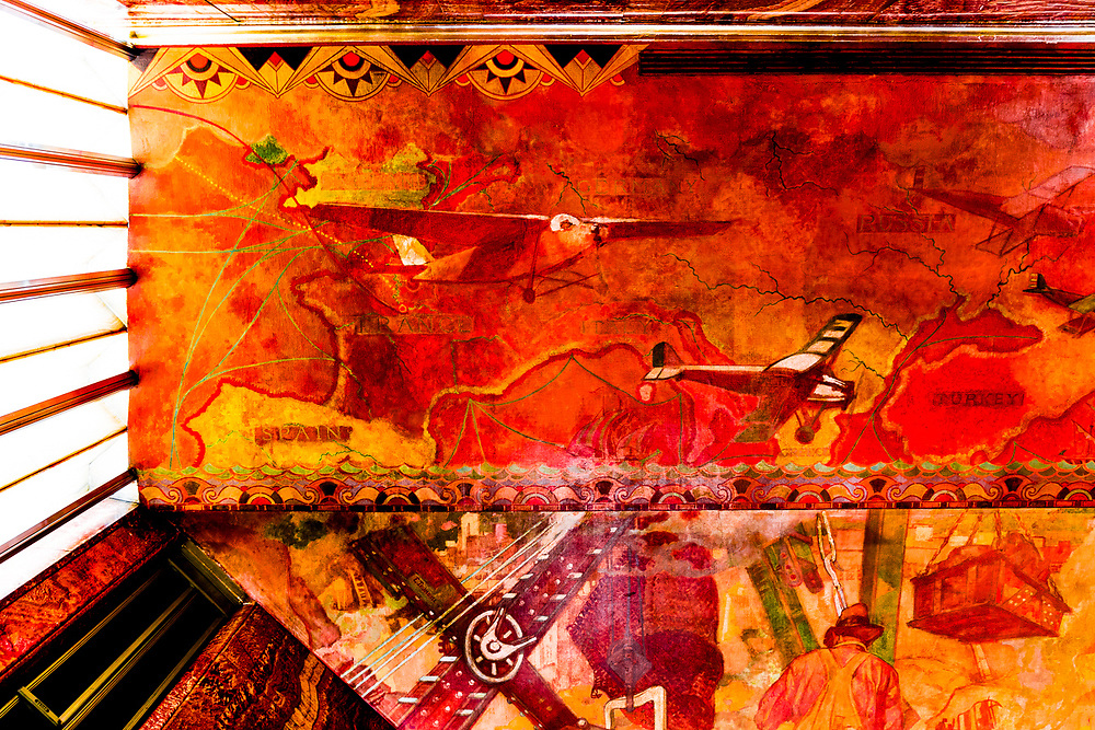 """This section of the huge """"Transport and Human Endeavor"""" mural on the ceiling and walls of the Chrysler Building's main lobby depicts scenes of heroic industrialism and early 20th Century transportation including the primitive but rapidly developing aircraft of the period.<br /> <br /> Some of the scenes are said to depict the construction of the Chrysler building itself.<br /> <br /> The canvas mural was painted by Edward Trumbull in 1929, but was given a polyurethane coating in 1970 that darkened it and made it hard to see until a costly restoration in 1999.<br /> <br /> This photo was made with the camera pointed straight up at the ceiling."""