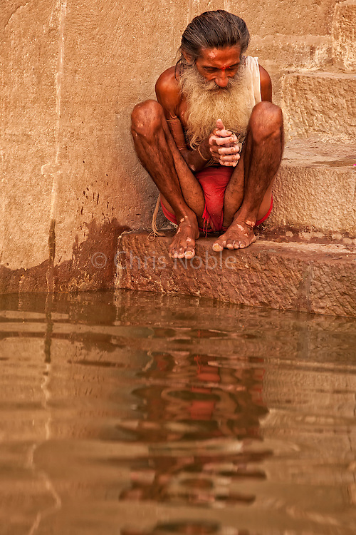 An elderly Hindu man performing his morning ritual puja by bathing in the Ganges River, Varanasi India.