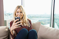 Smiling young woman reading text message at home