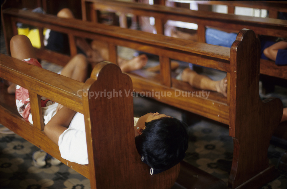 SIESTA IN THE SHADOW. VIGAN CATHEDRAL, LUZON ISLAND, THE PHILIPPINES