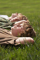 Three teenage brothers (13-17) lying down on front lawn close up