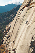 High angle view of a climber climbing a granite slab in El Hueso, La Pedriza, Madrid