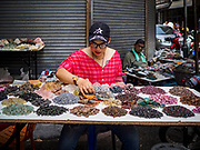22 DECEMBER 2018 - CHANTABURI, THAILAND: A woman selling unpolished gems and semi-precious stones in the gem market in Chantaburi. The gem market in Chantaburi, a provincial town in eastern Thailand, is open on weekends. Chantaburi used to be an active gem mining area in Thailand, but the mines are played out now. Now buyers and sellers come from around the world to Chantaburi for the weekend market. Many of the stones come from Myanmar, others come from mines in Afghanistan and Africa.      PHOTO BY JACK KURTZ