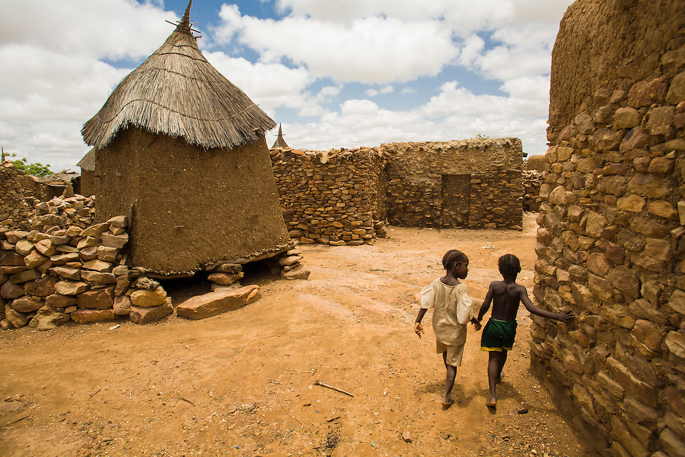 Children walking hand-in-hand in the Dogon village of Djiguibombo on the rocky plateau.  The Dogon Country is the most visited part of Mali with tourists visiting its tipical  villages that can be located on the cliff, on the sandy plain or in the rocky plateau.