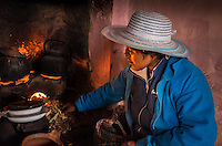 AMANTANI ISLAND, PERU - CIRCA APRIL 2014: Inhabitant of Amantani preparing food in a typical kitchen in a guest house of the Island.