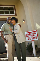 Middle-aged couple in front of new home