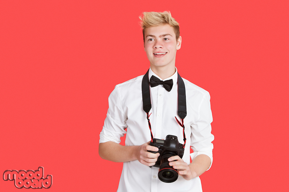 Handsome young man with digital camera over red background